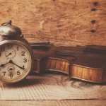 Antique clock and old violin over vintage wooden table