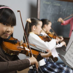 Asian girl playing violin in music class